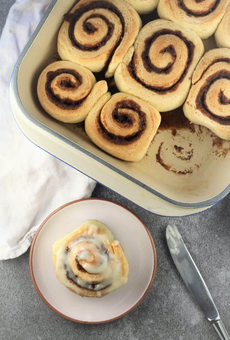 pan of brioche cinnamon rolls with one on plate with cream cheese icing