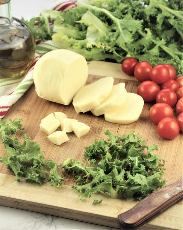 wood board filled with escarole, cheese, cherry tomatoes with knife on side