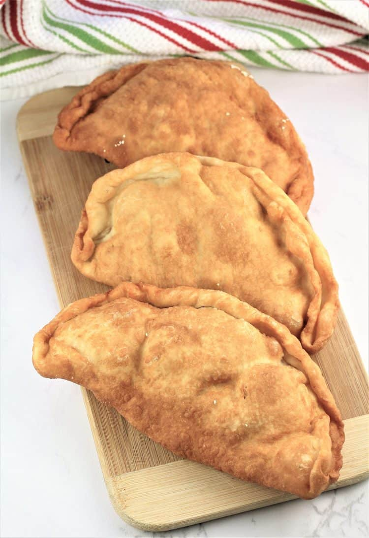 wood board covered with 3 pitoni Messinesi (Sicilian Fried Calzone) just out of the fryer