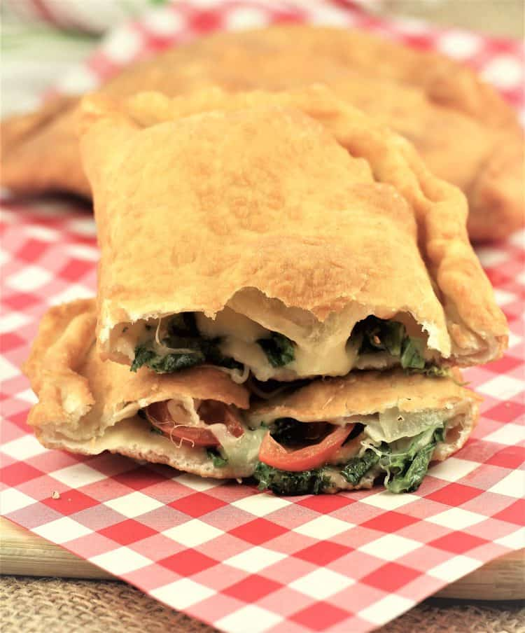 pitoni Messinesi (Sicilian Fried Calzone) cut in half to reveal escarole, tomato and cheese filling