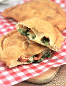 Pitoni Messinesi (Sicilian Fried Calzone) cut in half to reveal filling on red and white checked paper