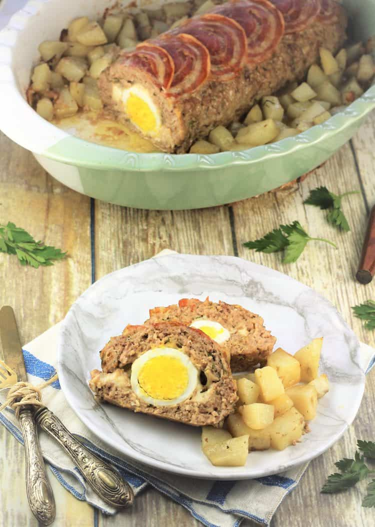 sliced polpettone with hard boiled eggs on plate surrounded by roast potatoes and whole meatloaf in roasting pan behind it