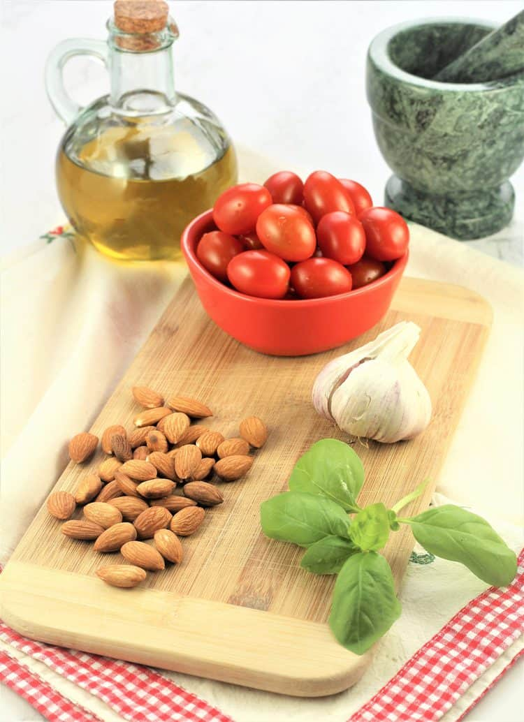 bowl of cherry tomatoes, almonds, basil leaves, olive oil and mortar and pestle