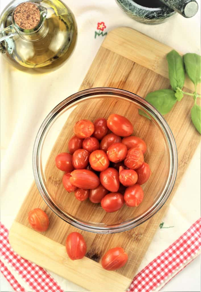 bowl of blanched tomatoes surrounded by basil leaves and olive oil