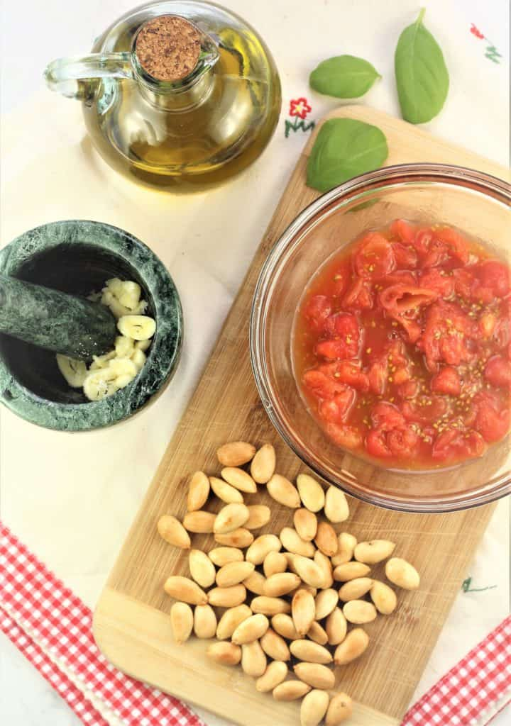 blanched almonds, chopped tomatoes in bowl, mortar and pestle with garlic and olive oil bottle
