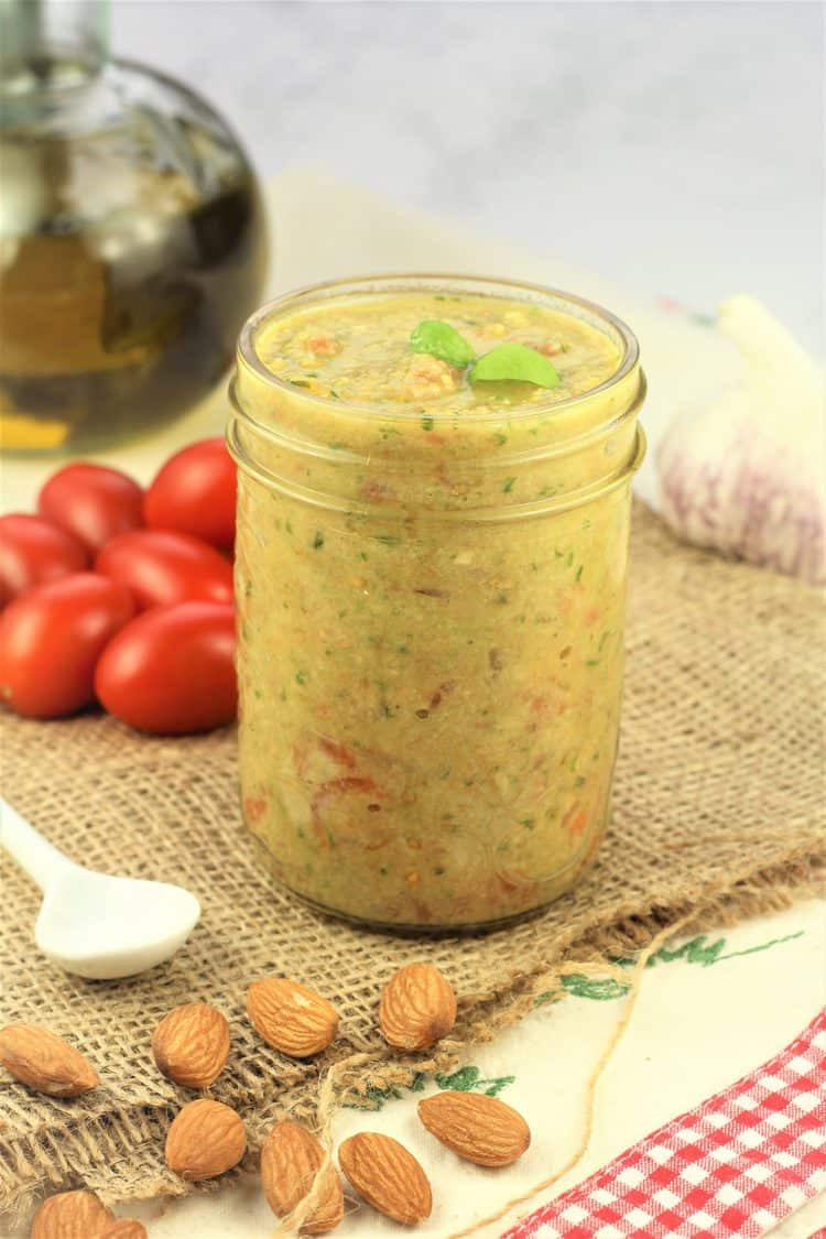 glass jar filled with pesto all Trapanese surrounded by almonds, cherry tomatoes, garlic and olive oil