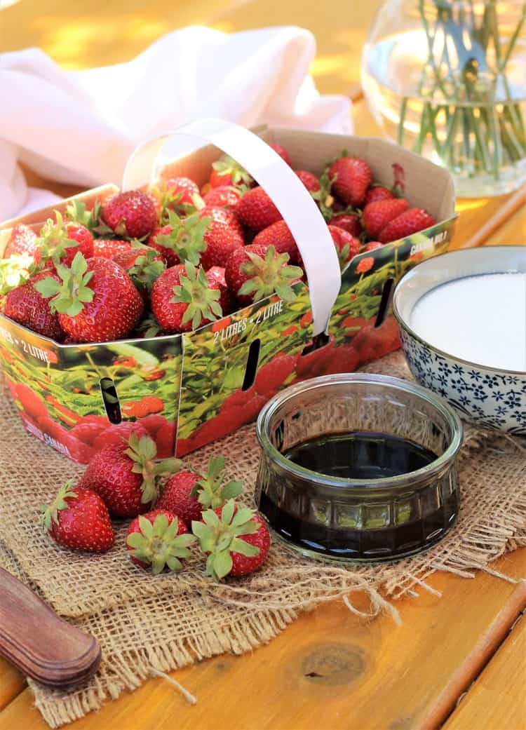 basket of strawberries, bowl of balsamic vinegar and bowl of sugar on wood board