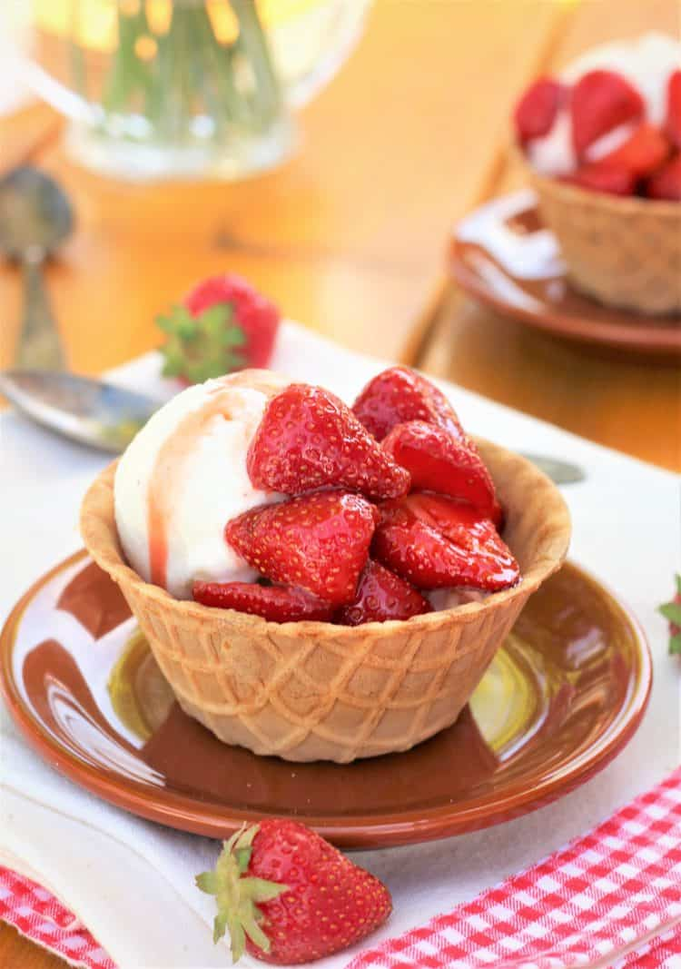 Balsamic Strawberries with Vanilla Ice Cream in waffle cone cup on brown plate