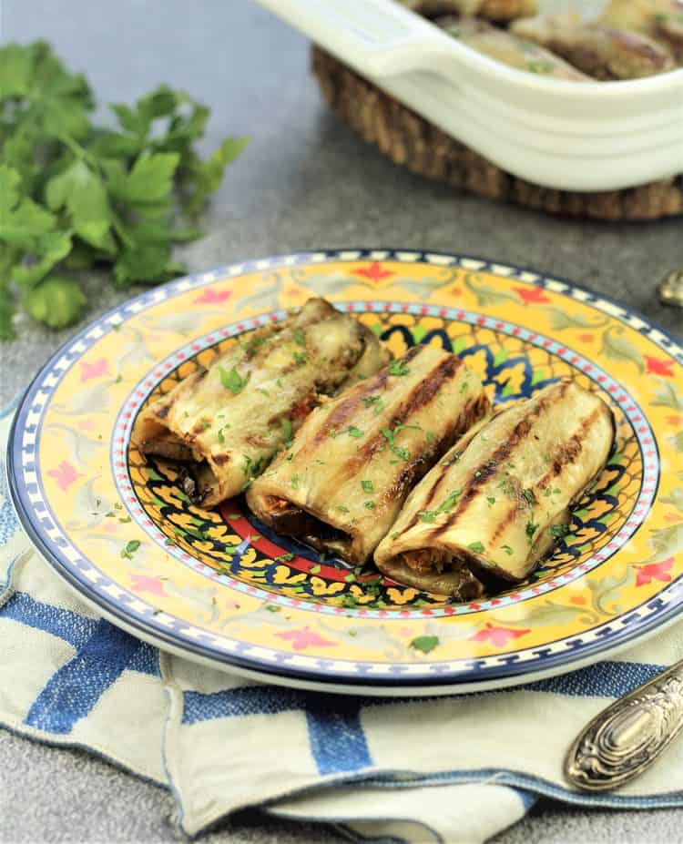 3 Grilled Eggplant Involtini on a multicolored plate on blue and white napkin