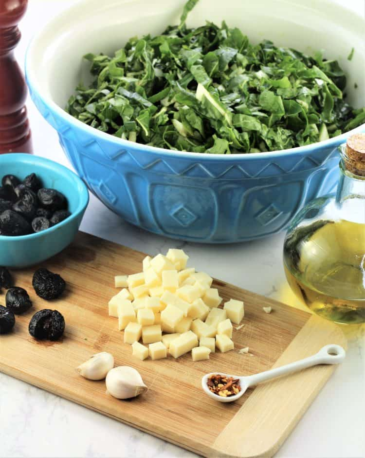 chopped swiss chard in large blue bowl with cubed cheese, black olives and olive oil flask in forefront