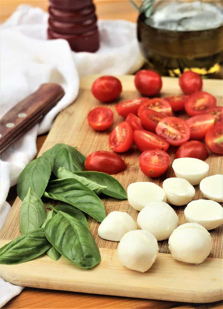 wood board with halved cherry tomatoes, mozzarella balls and basil leaves
