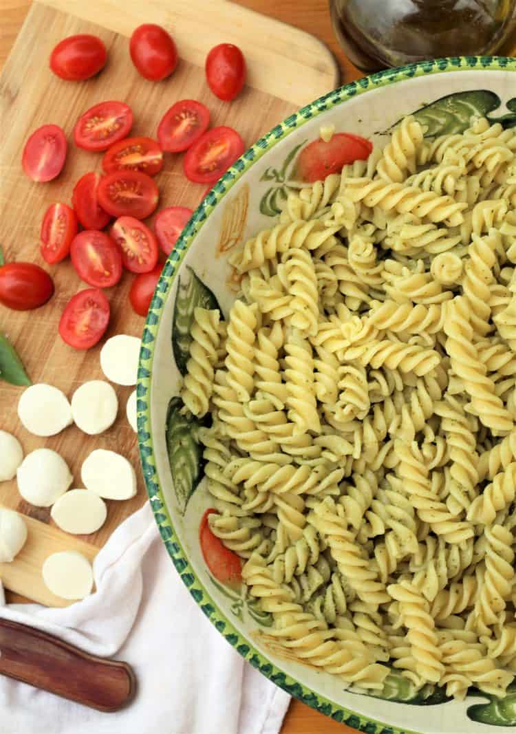 fusilli pasta with pesto in large salad bowl with cherry tomatoes and mozzarella on wood board on side