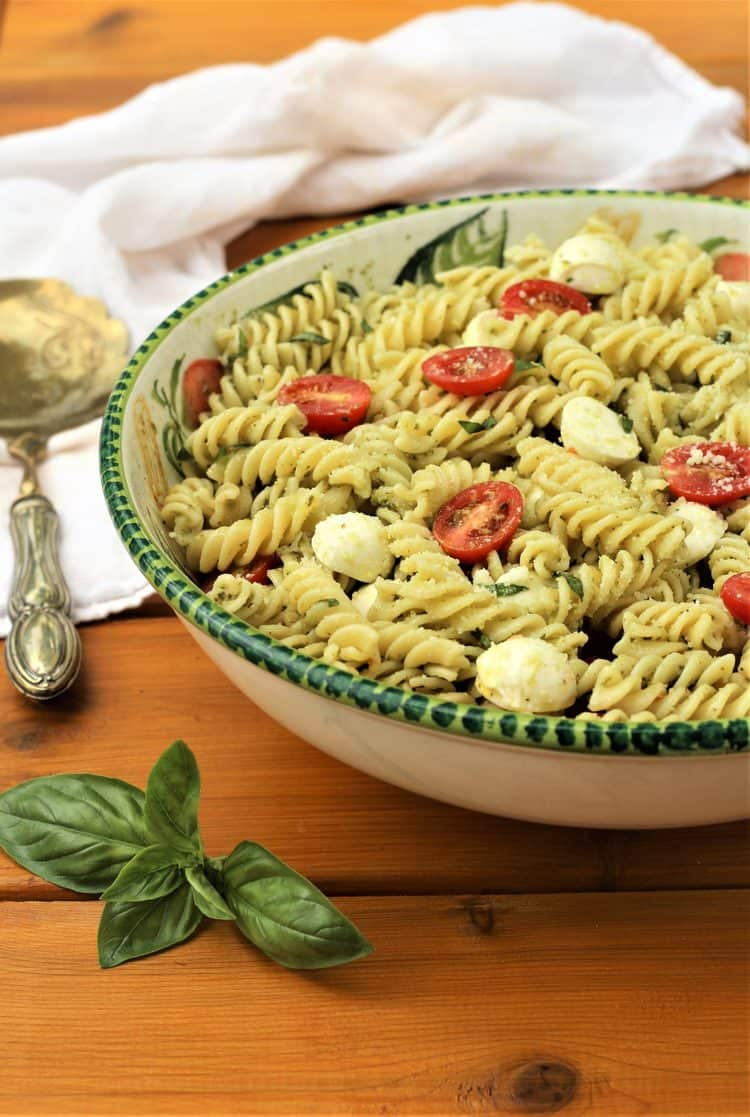 large bowl filled with Caprese Pasta Salad with Pesto on wood table with basil leaves in forefront