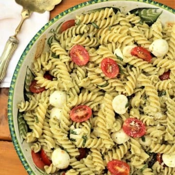 large salad bowl with Caprese pasta salad with pesto and serving spoon on side