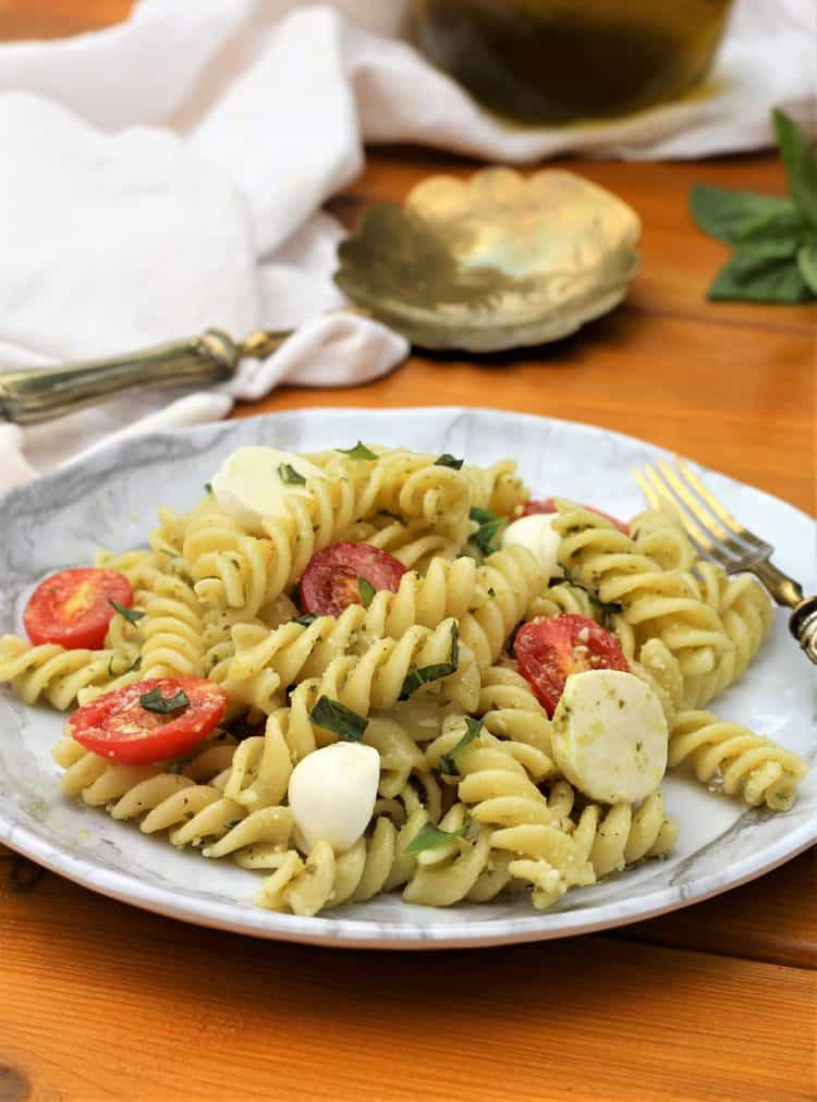 white plate filled with Caprese Pasta Salad with Pesto on wood table