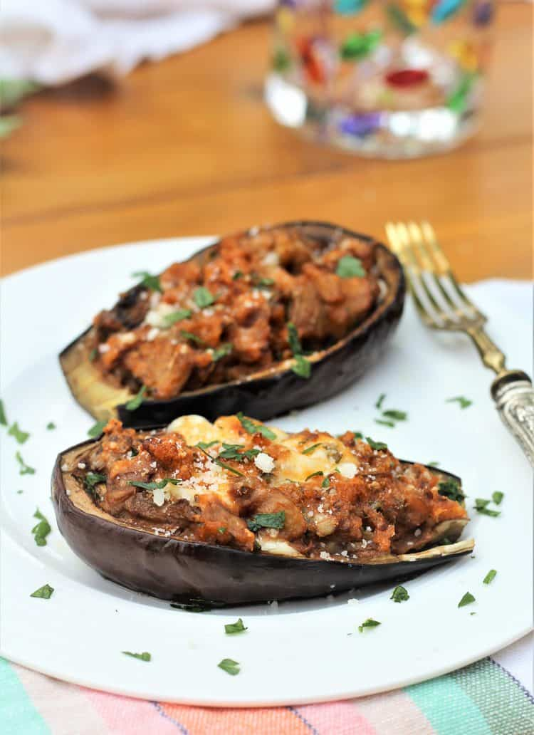 Stuffed Baby Eggplant on white plate with fork on side and glass in background