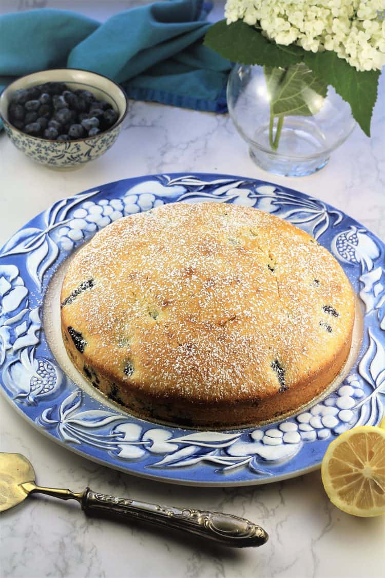 Blueberry Olive Oil Cake on blue and white cake plate with lemon wedge and bowl of blueberries