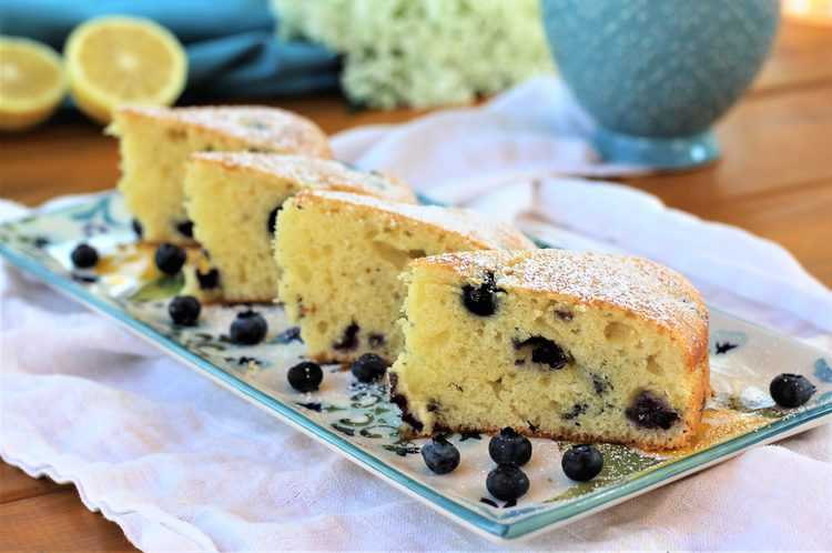 3 slices of Blueberry Olive Oil Cake on rectangular serving plate with lemon wedges in background