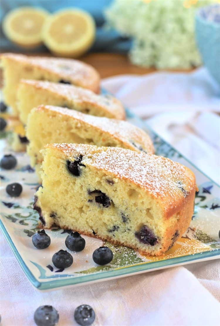 3 slices of blueberry olive oil cake on rectangular plate with lemons in background