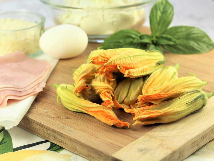 zucchini blossoms on wood board with basil leaves, an egg, ham slices and bowl with ricotta