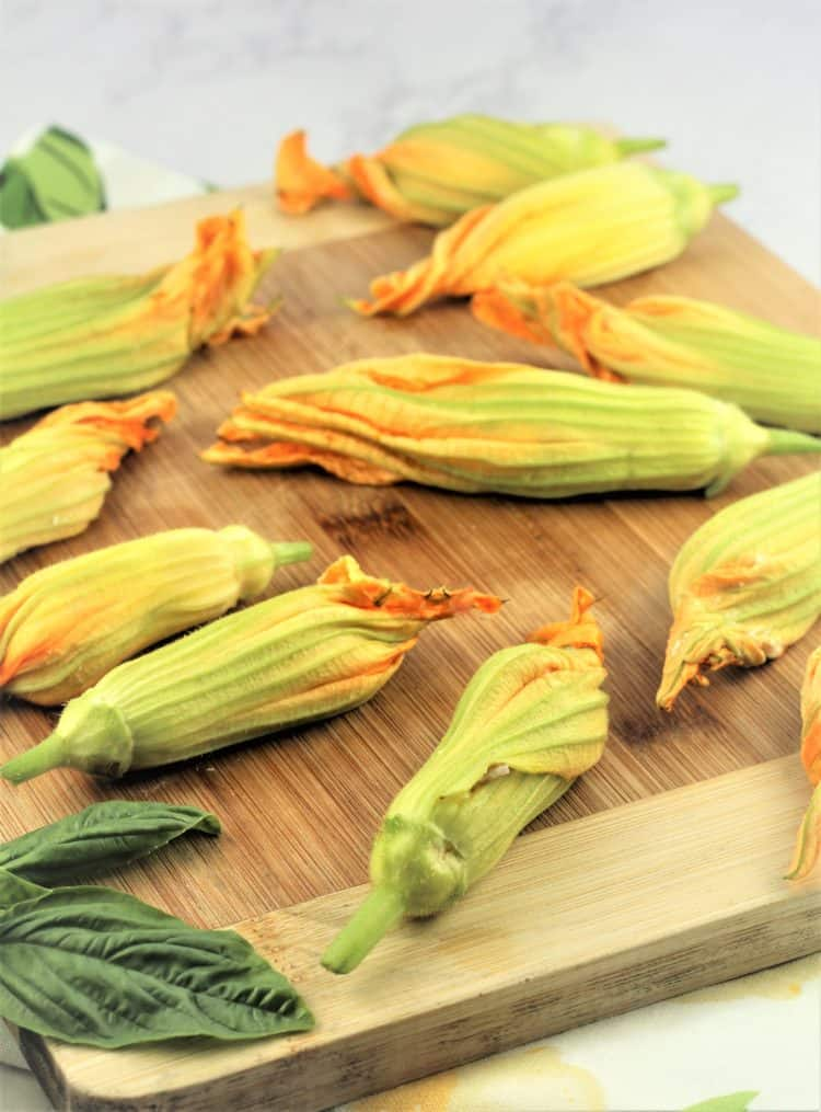 wood board covered with stuffed zucchini blossoms