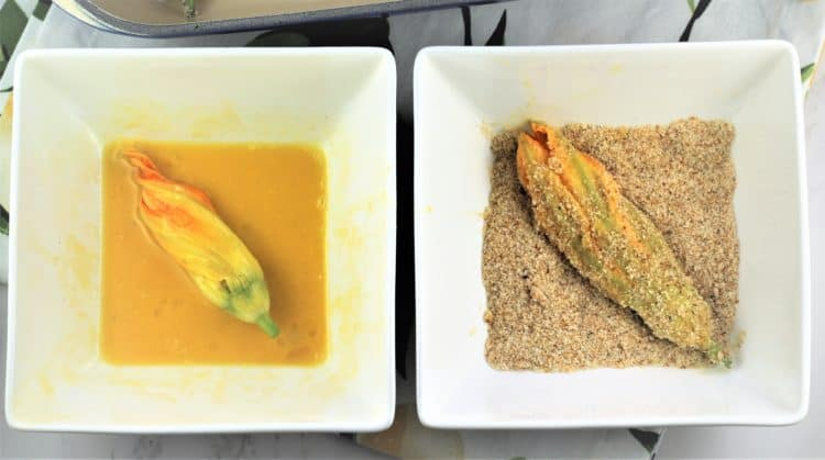 dredging zucchini blossoms in egg wash and bowl with breadcrumbs