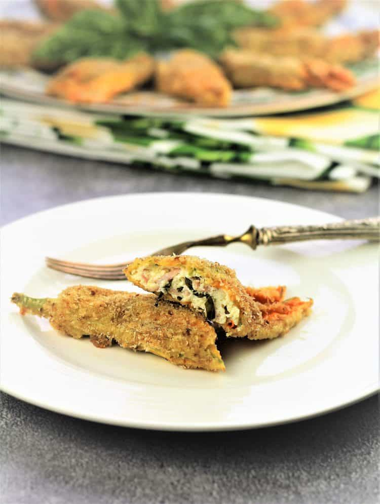 baked stuffed zucchini blossom cut in two on white plate with fork