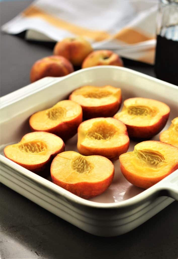 halved peaches in square white baking dish