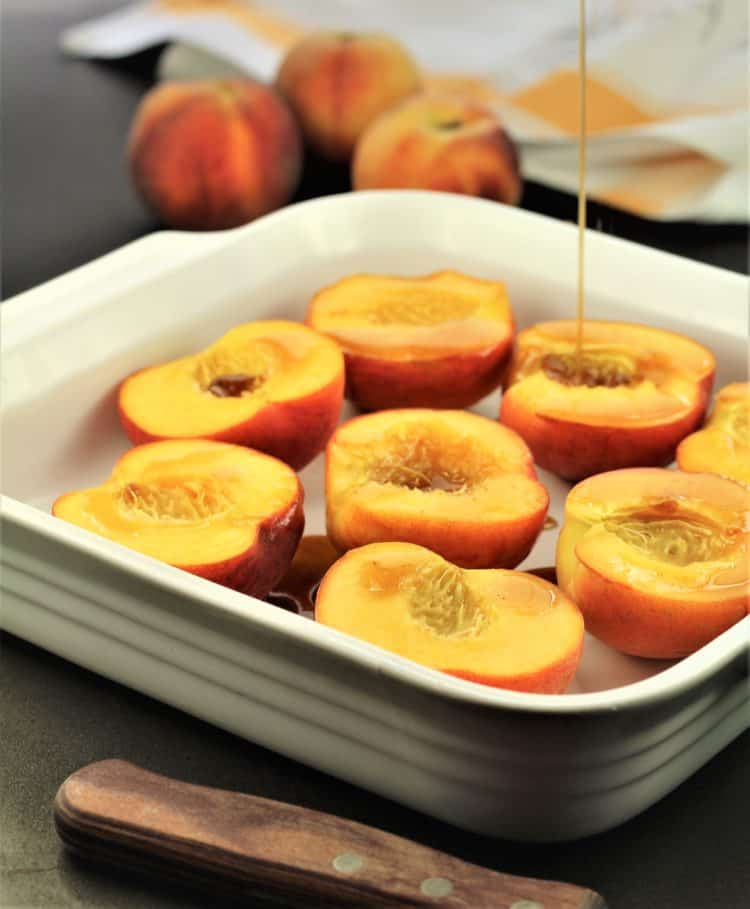 drizzling maple syrup on halved peaches in white square dish
