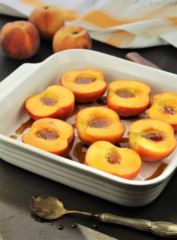 halved peaches in white square baking dish with maple syrup drizzled over them