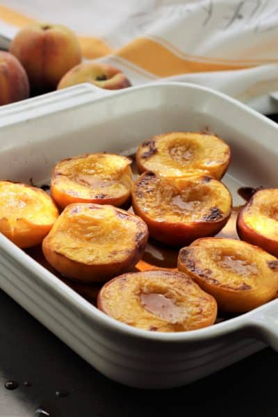maple roasted peach halves in square baking dish