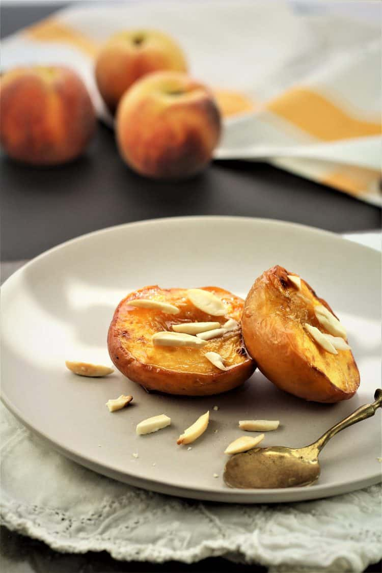 2 maple roasted peach halves topped with slivered almonds on plate with spoon