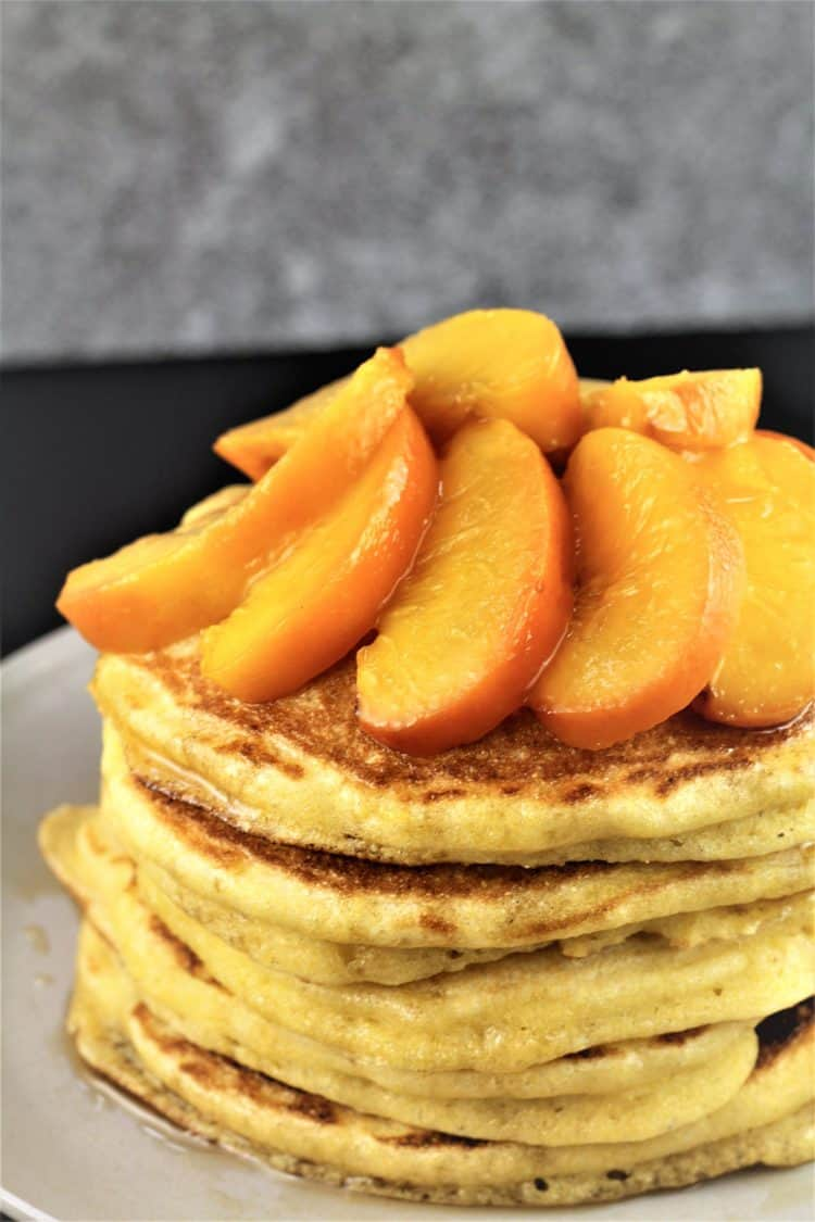 sliced maple roasted peaches on a stack of pancakes