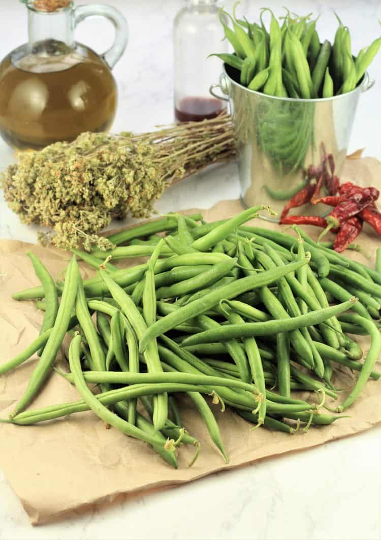 pile of green beans, dry oregano, dried chili, olive oil bottle