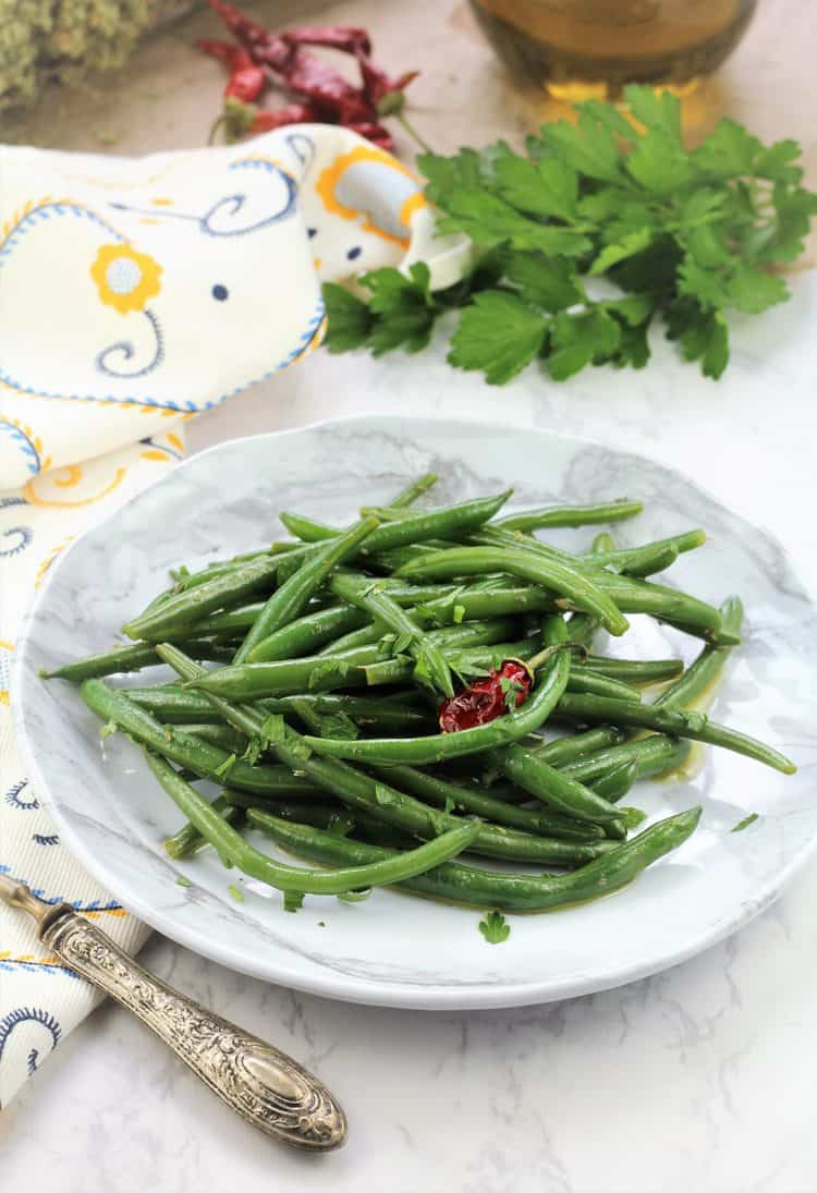 green bean salad in white plate with fork on side