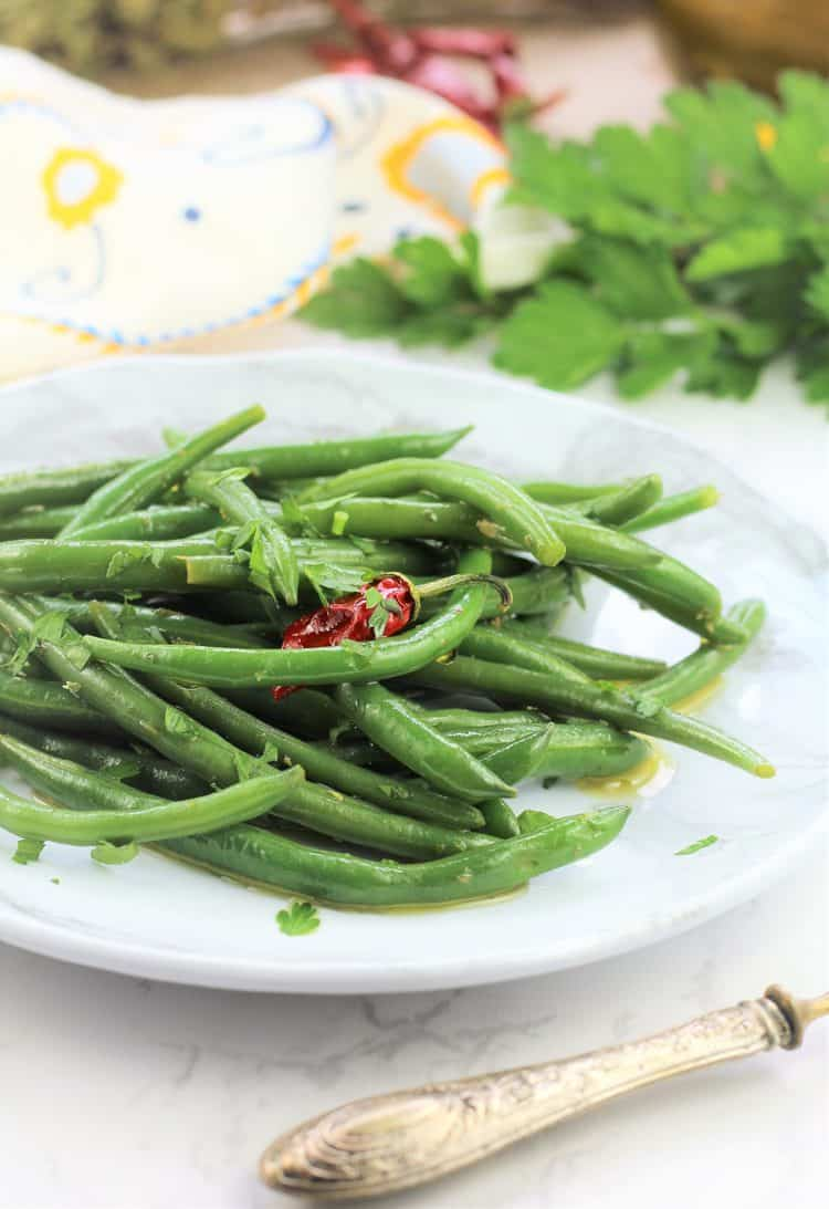 Italian green bean salad on white plate with parsley in background