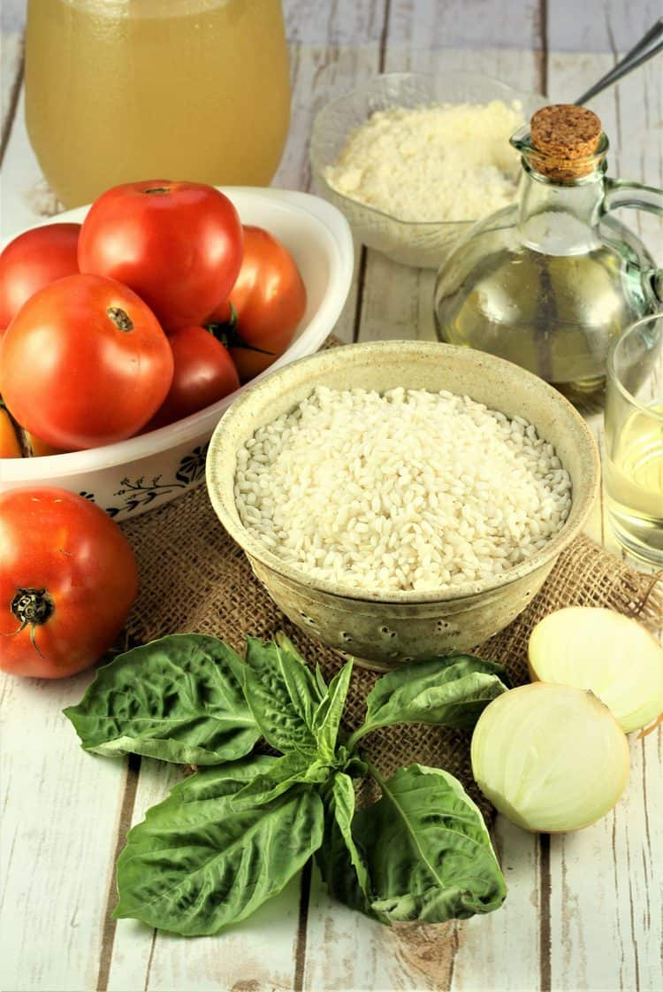 bowl of rice, tomatoes, basil leaves, halved onion, olive oil and bowl of grated cheese