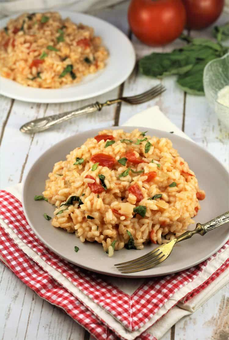 two plates with tomato basil risotto and forks on side, whole tomatoes and basil in background