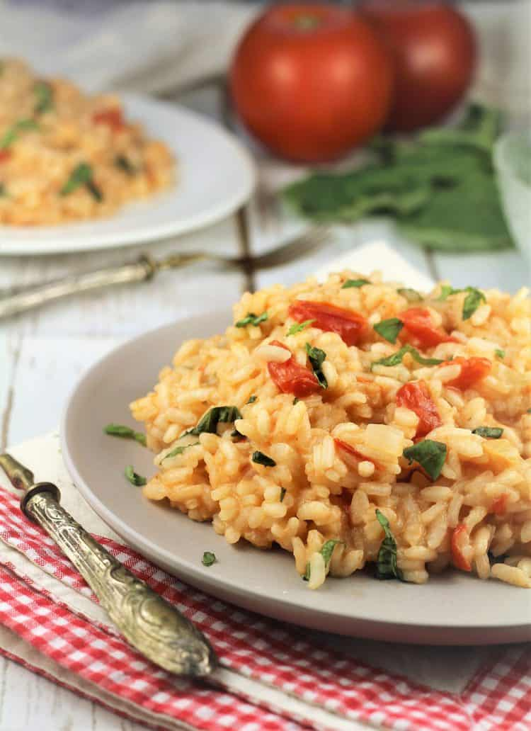 plate with tomato and basil risotto on red checkered dish cloth with tomatoes in background