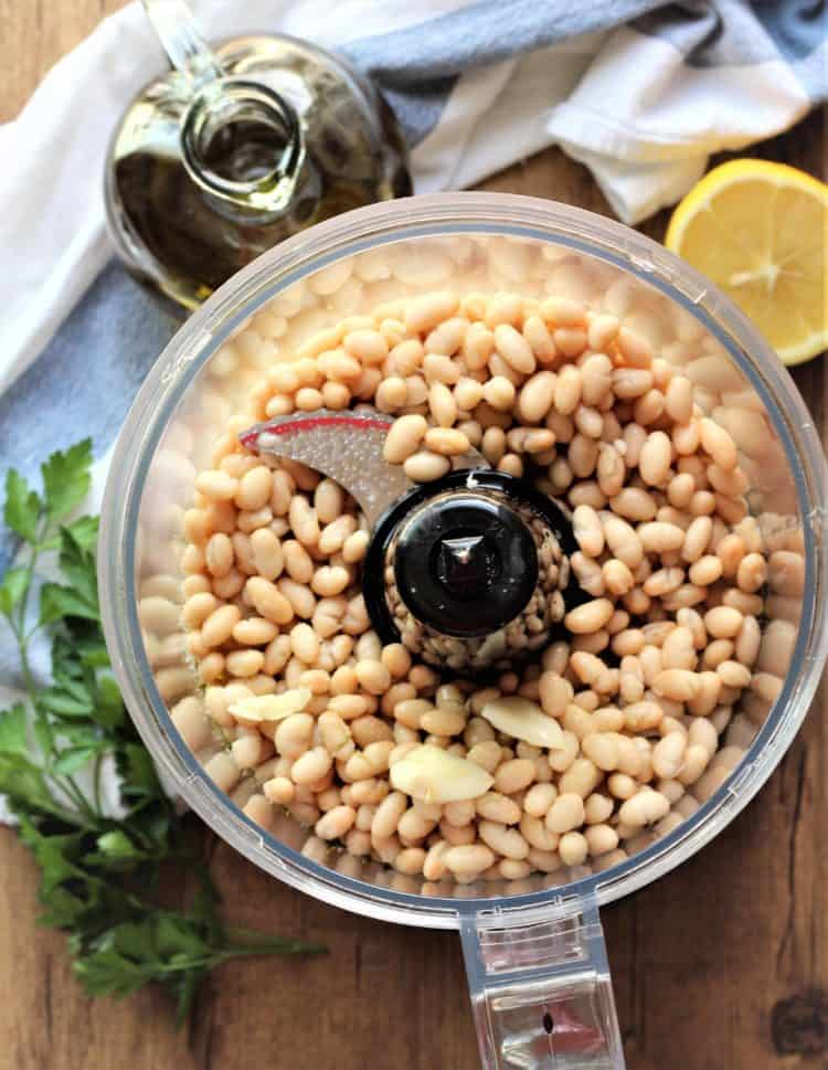 overhead view of food processor bowl filled with white beans, garlic clove