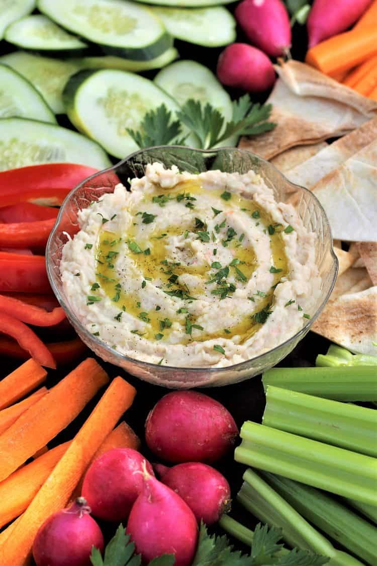 white bean dip in bowl surrounded by crudités