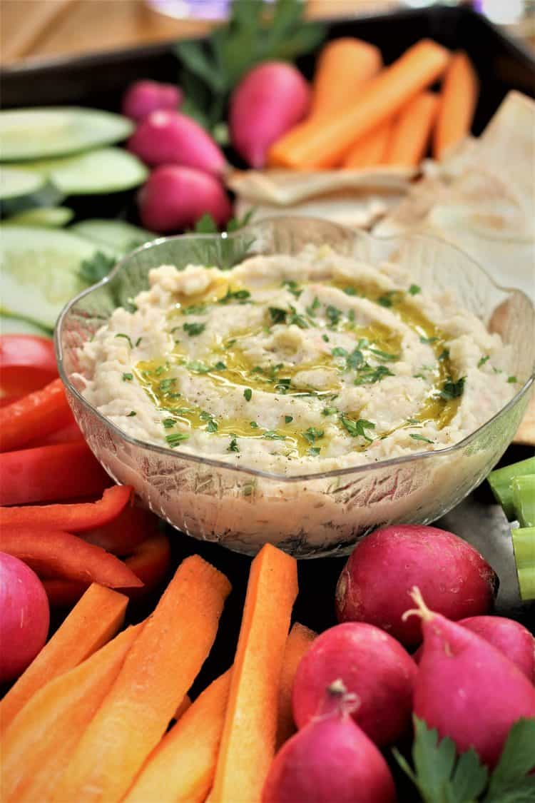 white bean dip in glass bowl surrounded by crudités