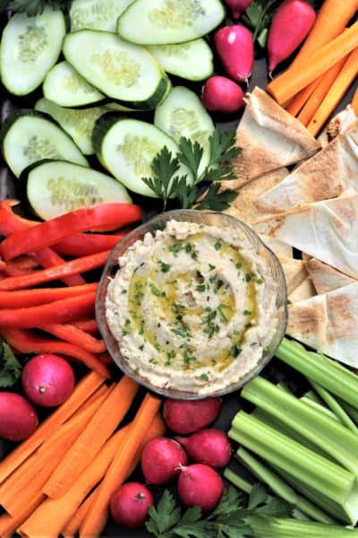 bowl of white bean dip surrounded by crudités