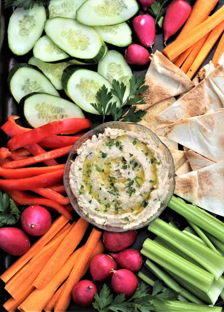 white bean dip in bowl surrounded by crudités and pita crisps