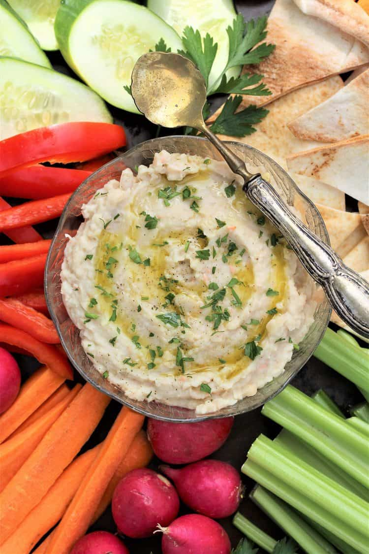 white bean dip in glass bowl with spoon over it surrounded by crudités