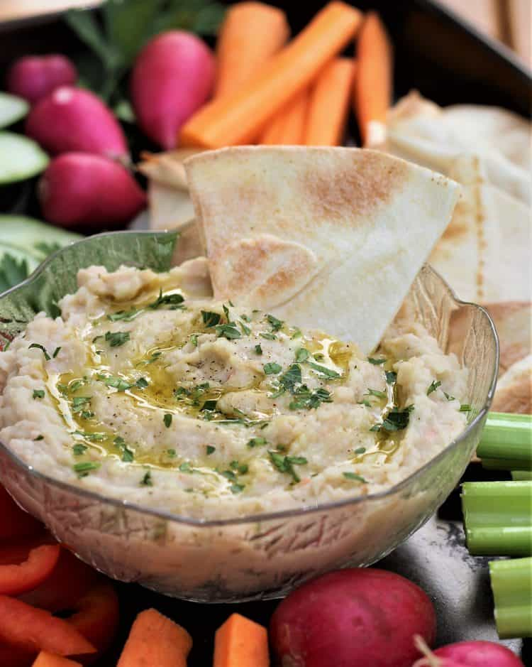 crispy pita wedge dipped in bowl with white bean dip