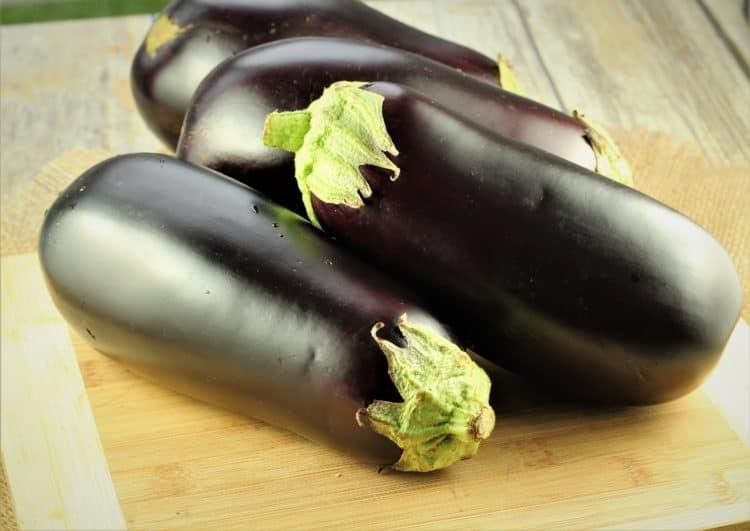 globe eggplants on cutting board