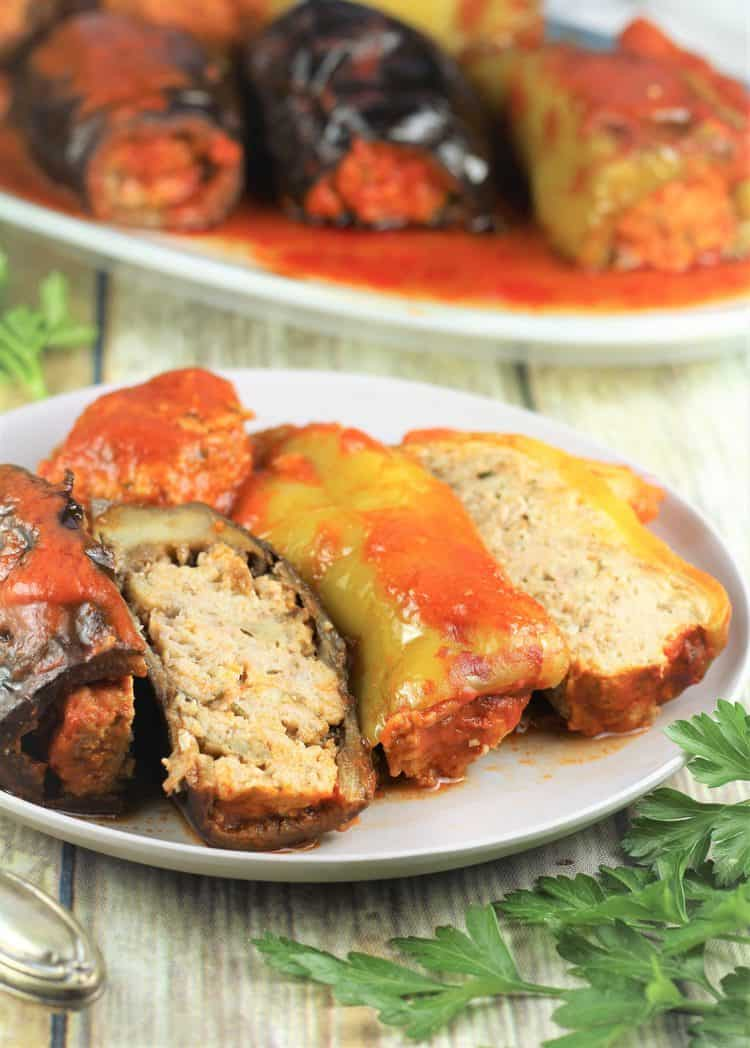 stuffed eggplant and pepper sliced in half on plate with serving platter behind it