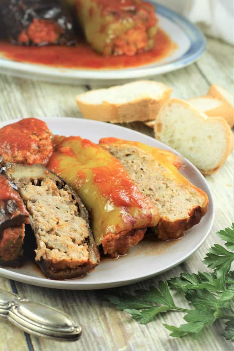 stuffed eggplant and pepper halves on plate with bread slices in background