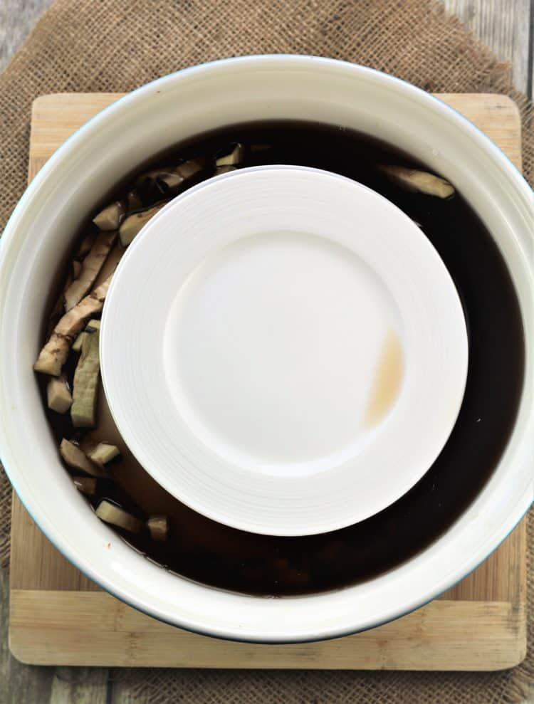 large bowl with eggplant soaking surrounded by dark water